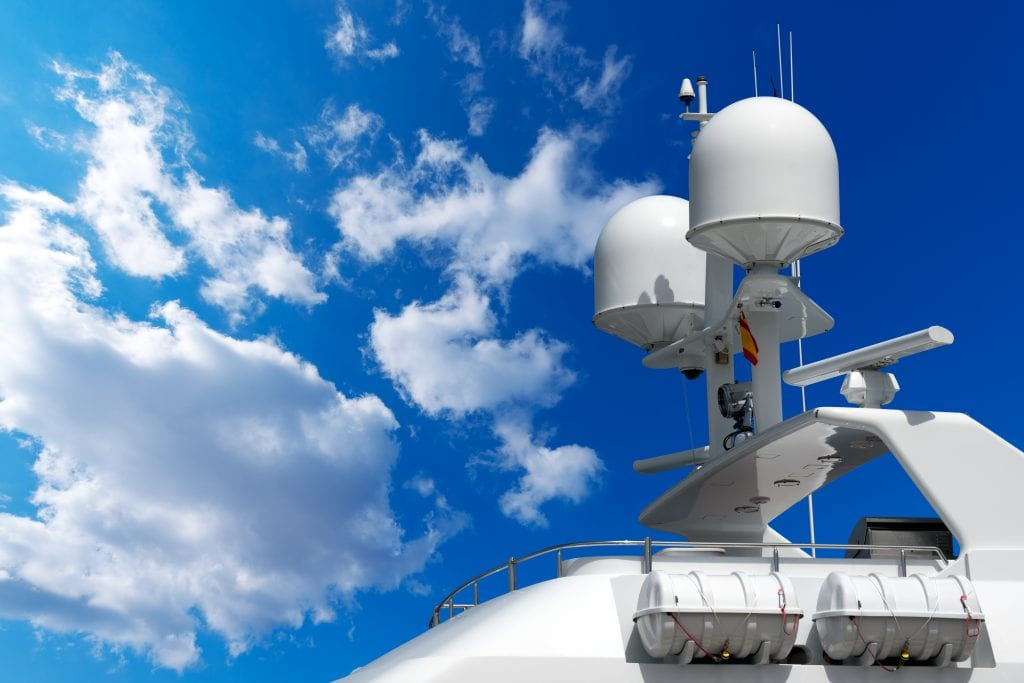Detail of luxury white yacht with navigation equipment, radar, antennas and lifeboats on blue sky with clouds